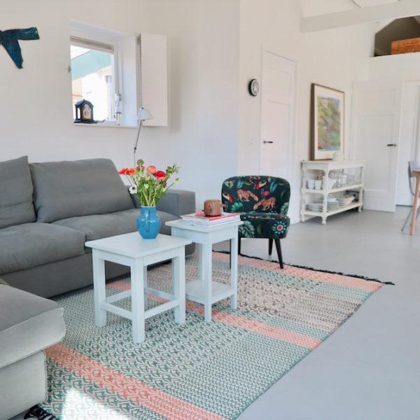 Lichte woonkamer met grijze bank, een gebloemd fauteuiltje en doorkijk naar eethoek