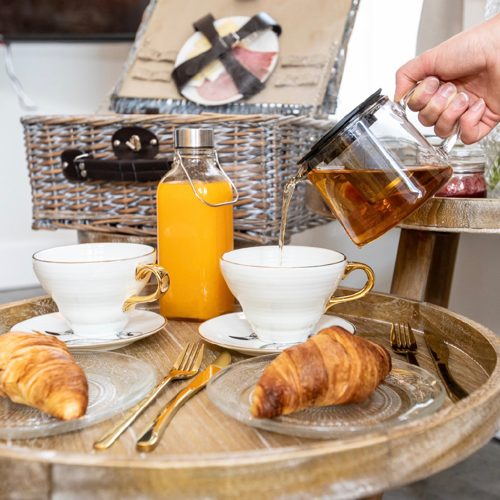 Thee inschenken boven een tafel met 2 borden, 2 kopjes, croissants en jus d'orange