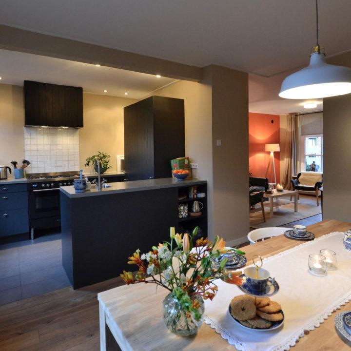 Eettafel met bloemen en zicht op de zwarte keuken en zithoek met oranje wand