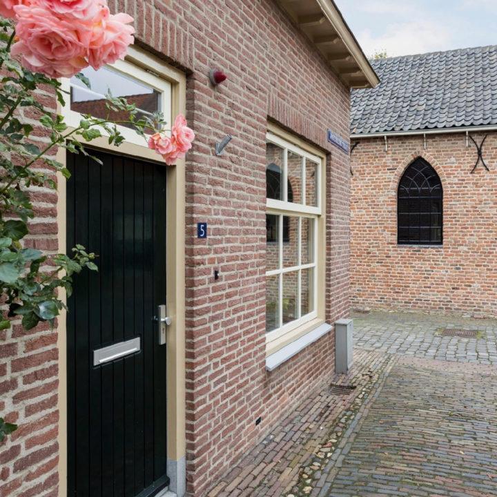 Voorzijde vakantiehuisje in Buren. De voordeur met roze rozen ernaast
