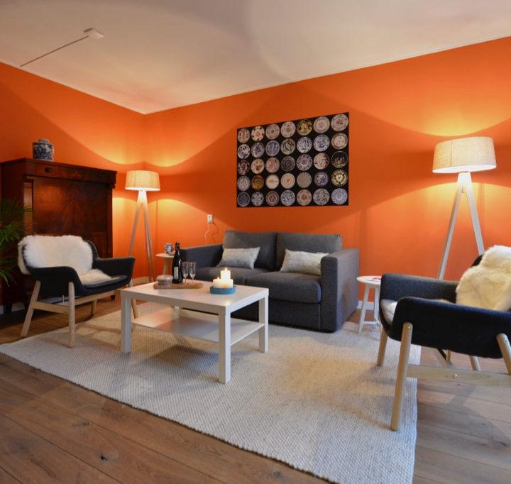 Kleurrijke woonkamer met oranje wand, bankstel en twee fauteuils in Huisje in Buren