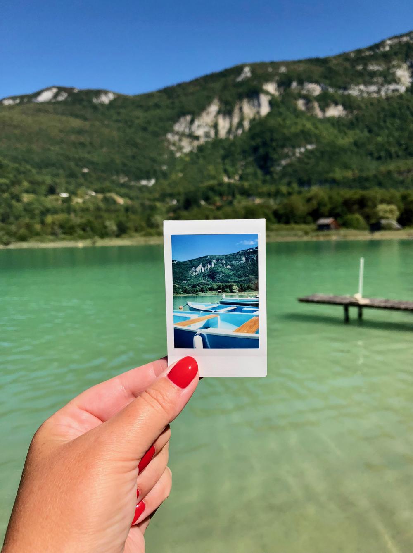 Hand met rode nagels houdt een polaroid vast voor een bergmeer met groen water