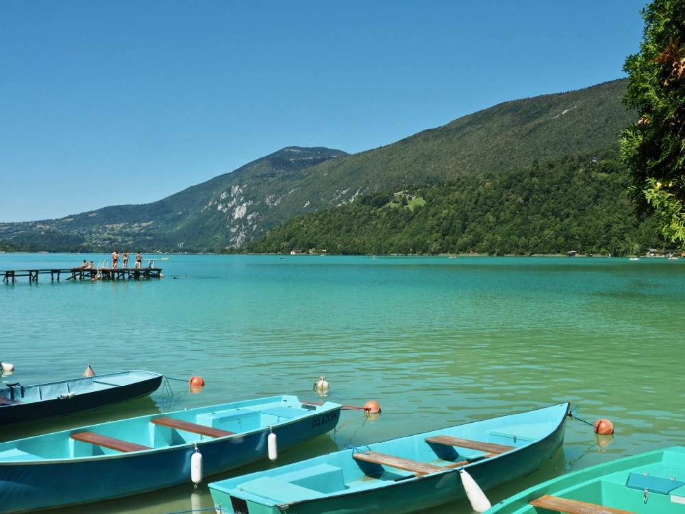 Groene en blauwe roeibootjes te huur. Op de achtergrond een steiger met zwemmende kinderen