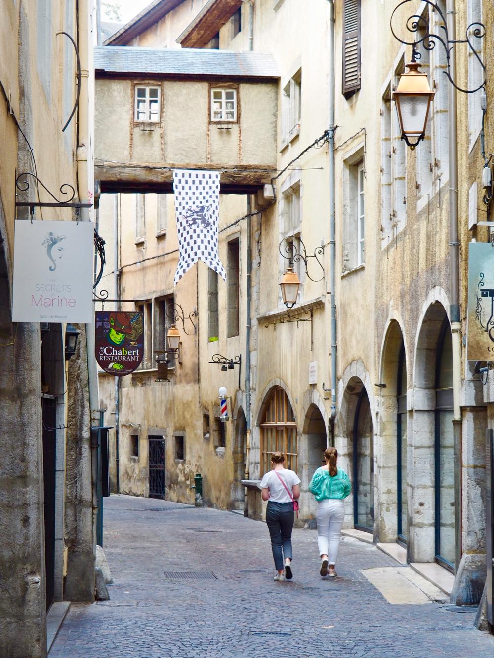Een smalle straat met eeuwenoude zandkleurige huizen, waarvan enkele verbonden met een brug