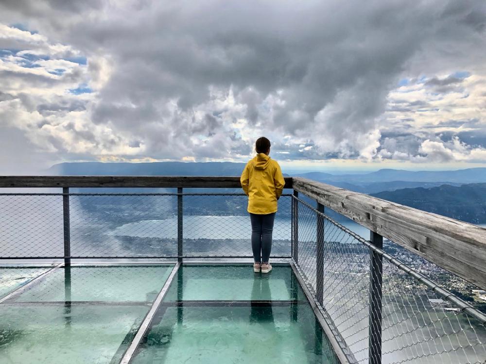 Een uitkijkpunt met glazen bodem met daarop een meisje met een gele regenjas die naar de bergen staart