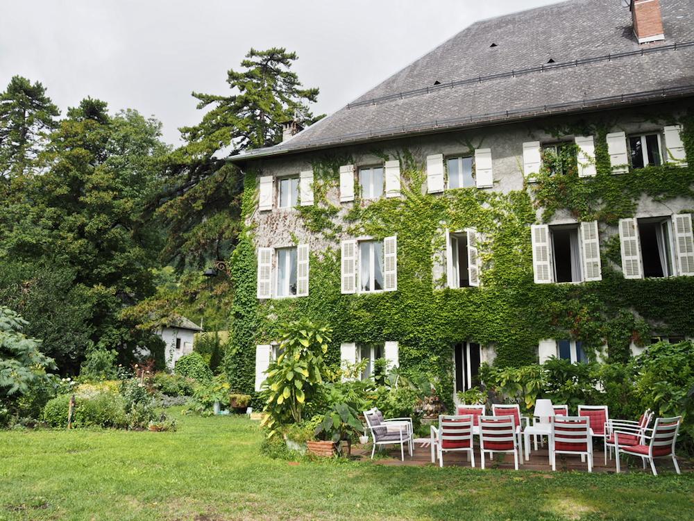 Buiten aanzicht van Chateau des Allues. Een gevel met grote ramen, veel groen eromheen in de tuin en een zittje