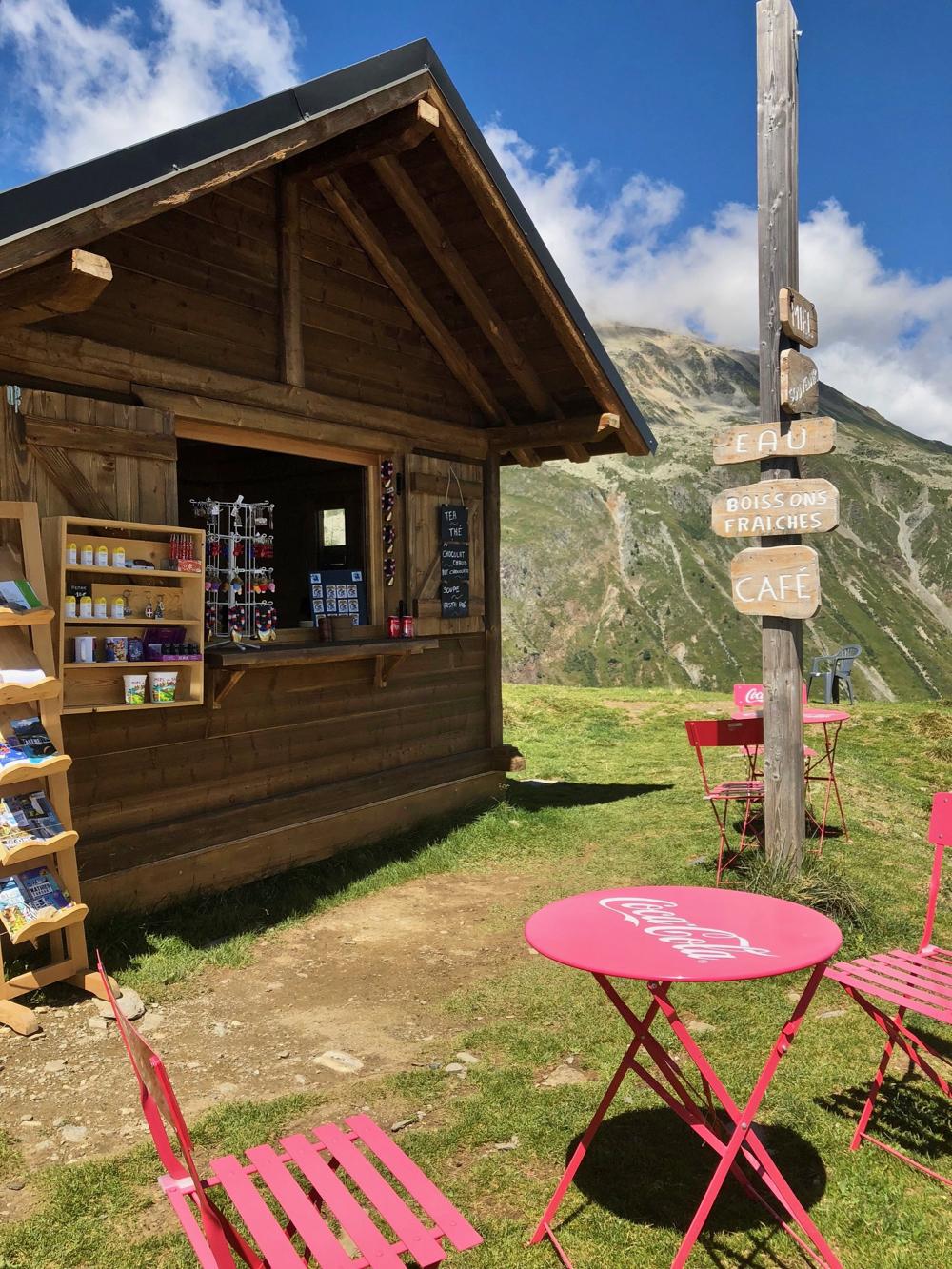 Rode coca cola stoeltjes voor een houten hutje waar je iets te drinken kunt kopen. Hoog in de bergen.