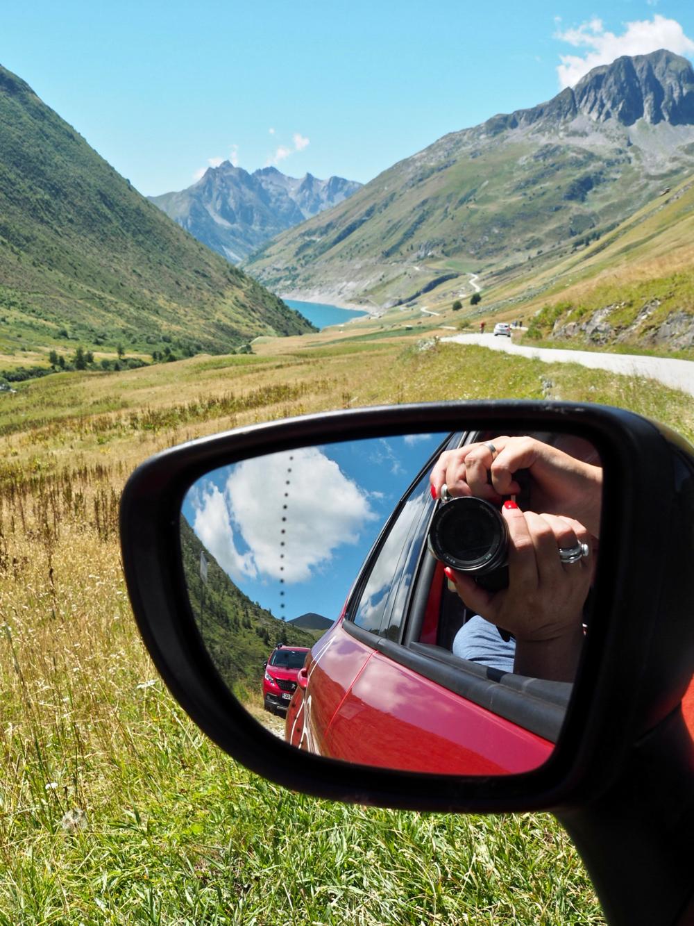 Autospiegel met het decor van de bergwereld erin. Op de achtergrond een stuwmeer