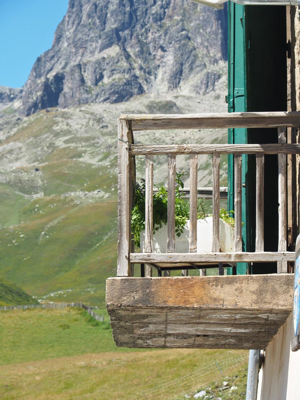 Hoog in de bergen een houten balkon met zicht op ruige toppen