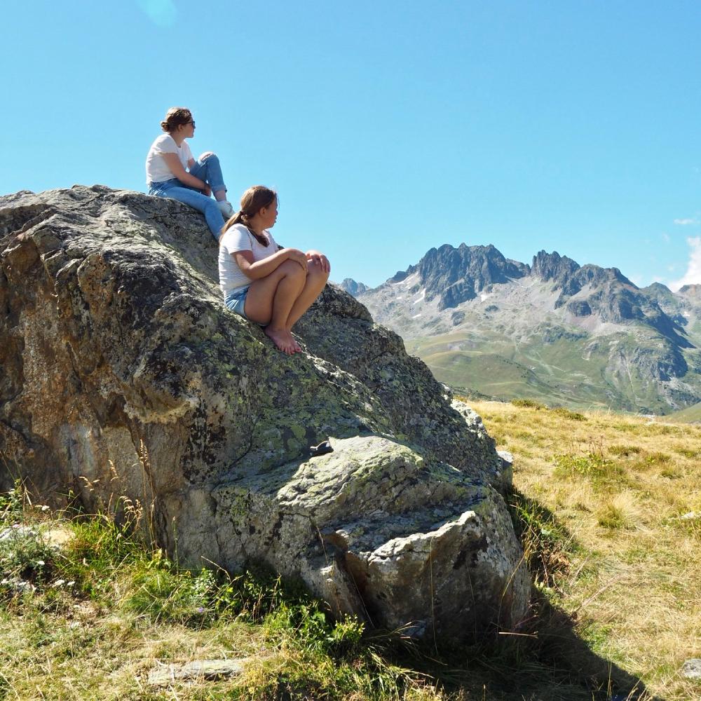 2 meisjes op een grote rots die de bergwereld bewonderen