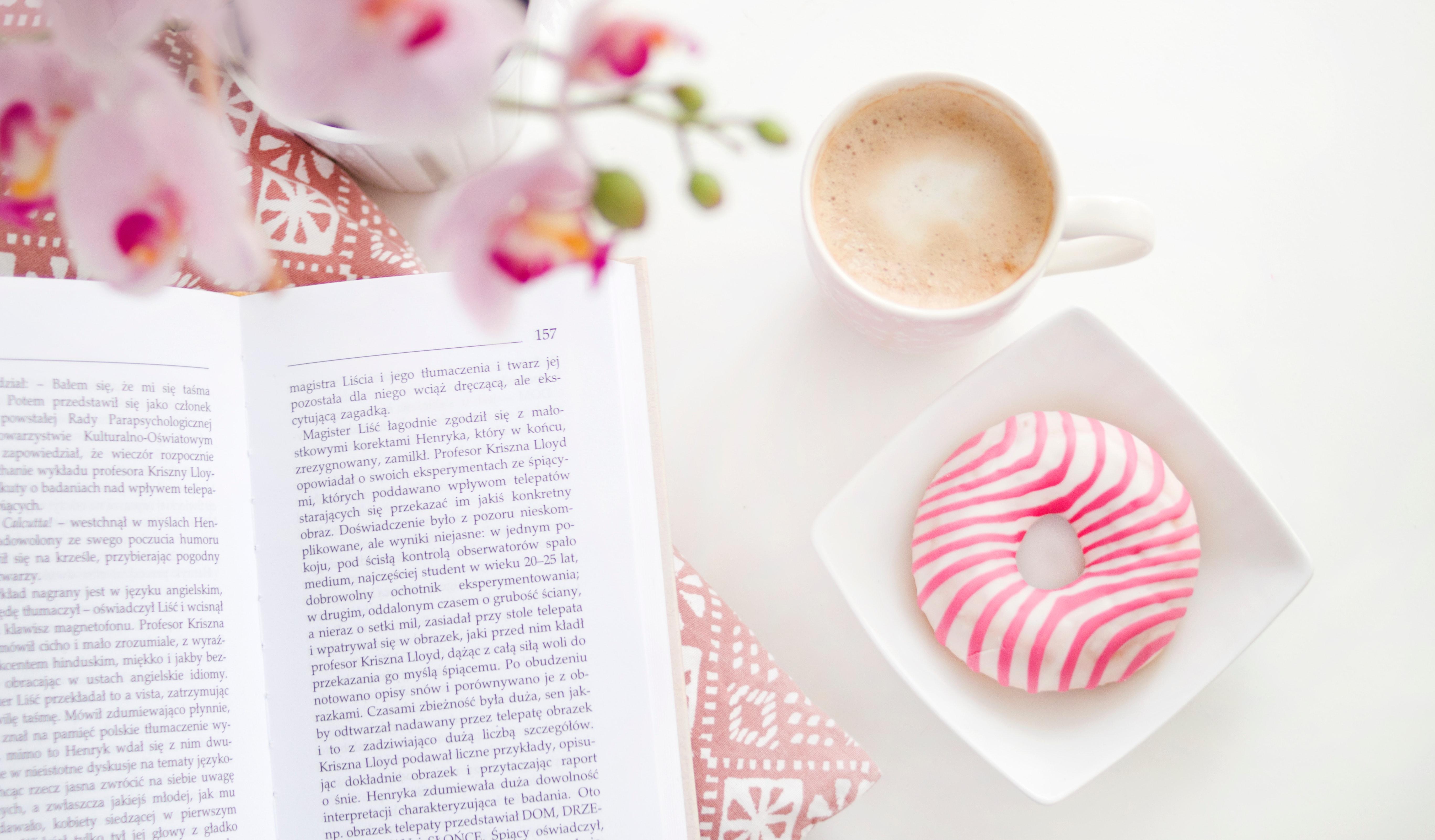 Boek op tafel met bloemetjes, een cappuccino en donut