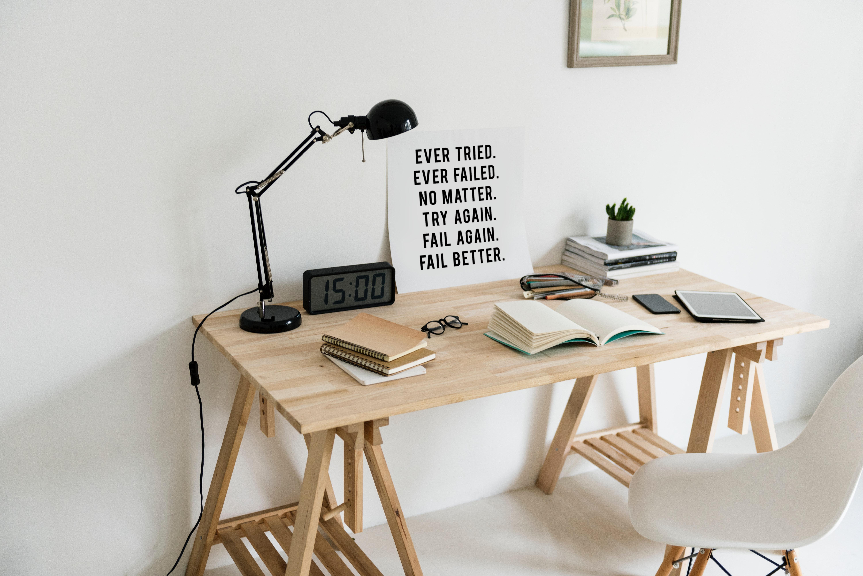 Een blank houten bureau met notitieboeken en bureaulamp