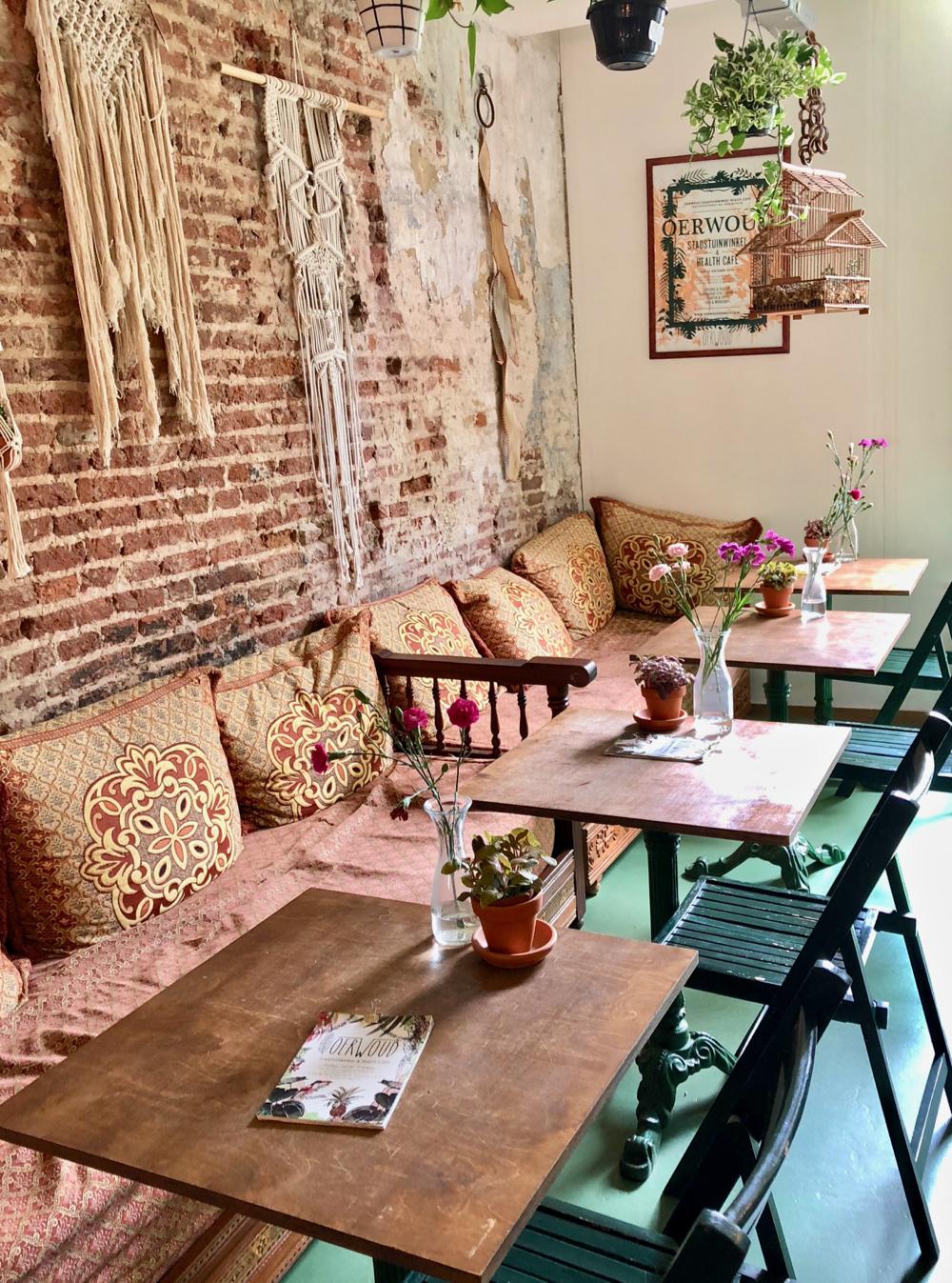 Cafe Oerwoud met een lange bank langs de wand, tafeltjes en stoeltjes en een ruwe stenen muur