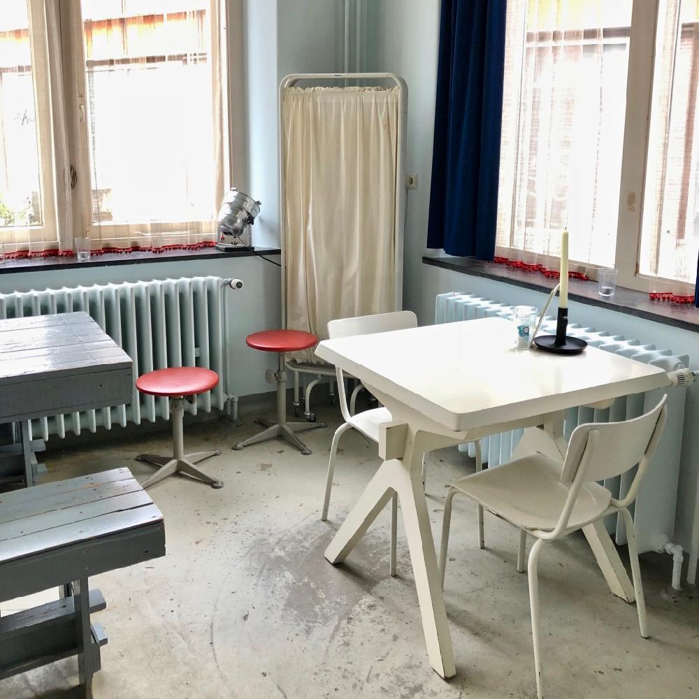 Witte tafel en stoeltjes voor het raam met op de achtergrond een ziekenhuis scherm