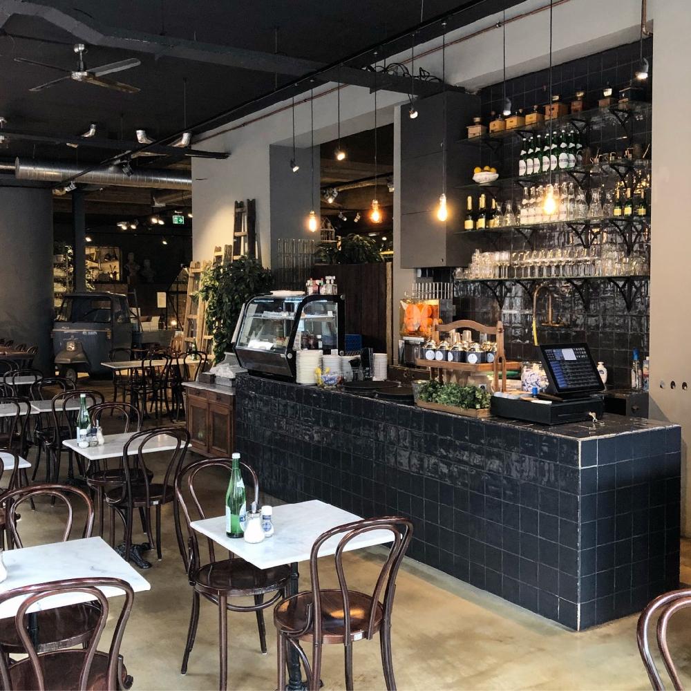 Franse marmeren tafels met houten stoeltjes en een zwart betegelde bar bij dit lekkere adres in Den Bosch