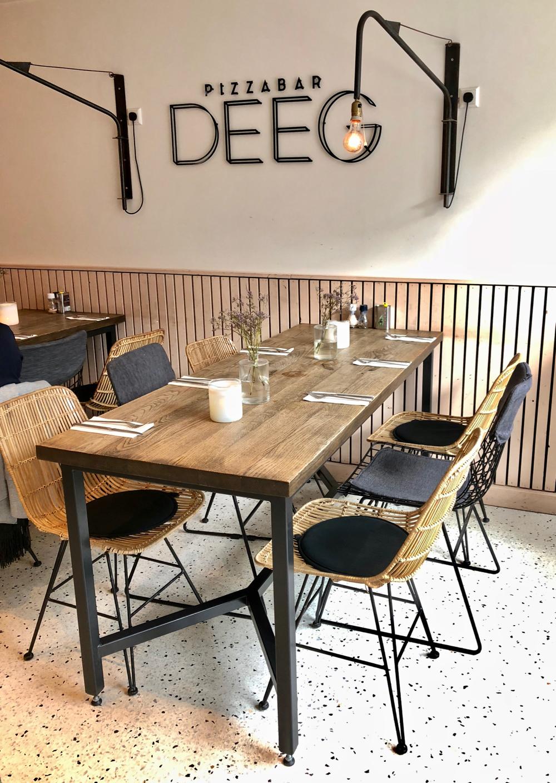 Interieur van DEEG, in grote letters aan de wand. Een houten tafel met stalen frame en stoeltjes van rotan en staal
