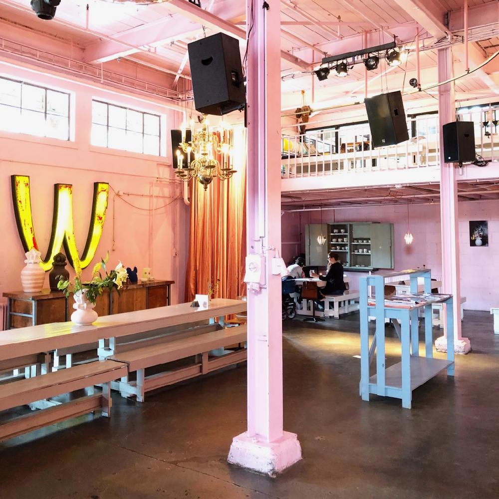Roze restaurant met lange tafels en een grote verlichte M aan de muur