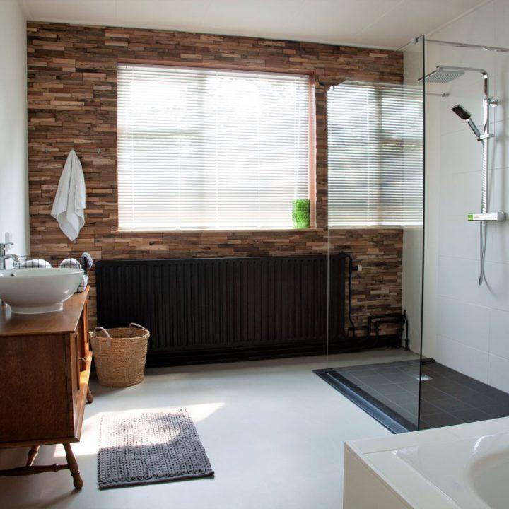 Badkamer met betonnen vloer, ligbad, inloopdouche