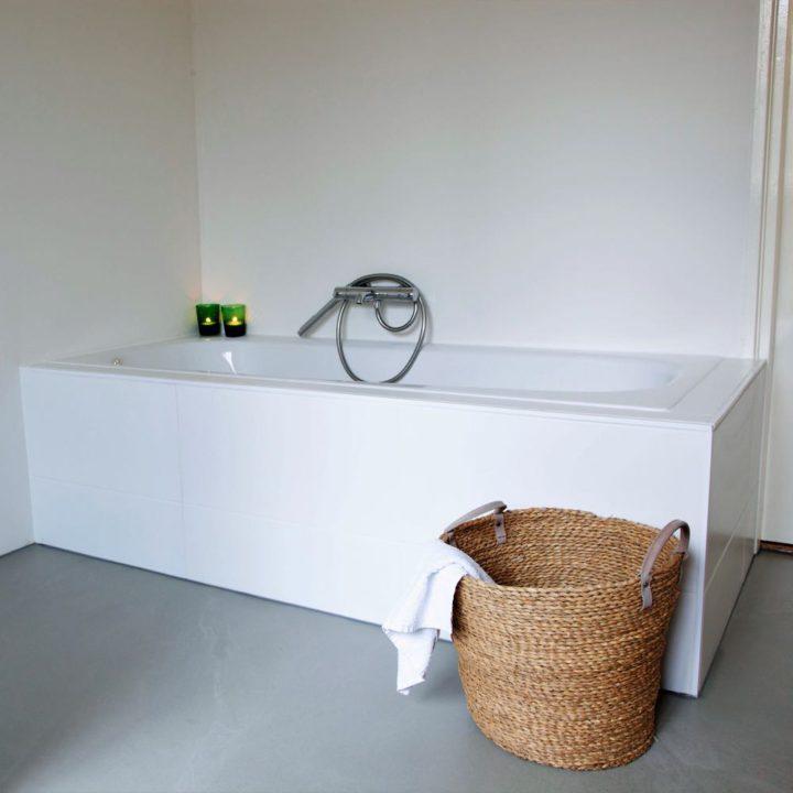 Wit ligbad, betonnen vloer en een rieten mand voor het bad