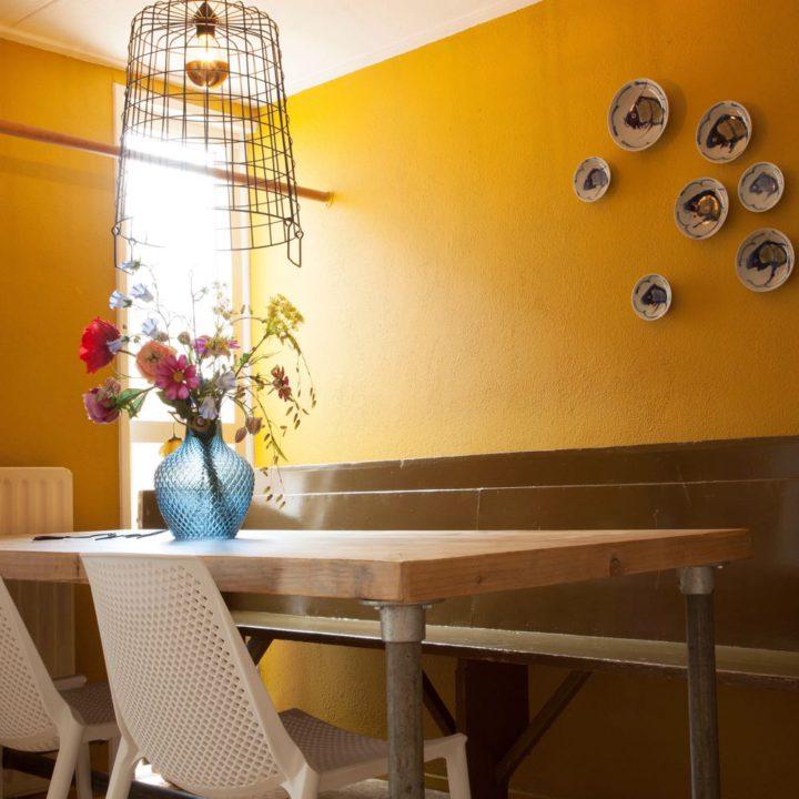 Eettafel van steigerhout, witte stoelen en een gele wand