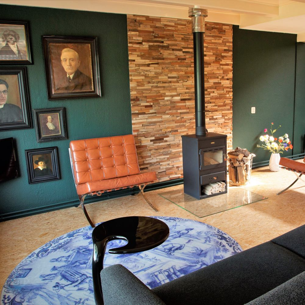 Woonkamer met zeegroene wand met vintage schilderijen, een bruine leren design stoel, houtkachel en design vloerkleed