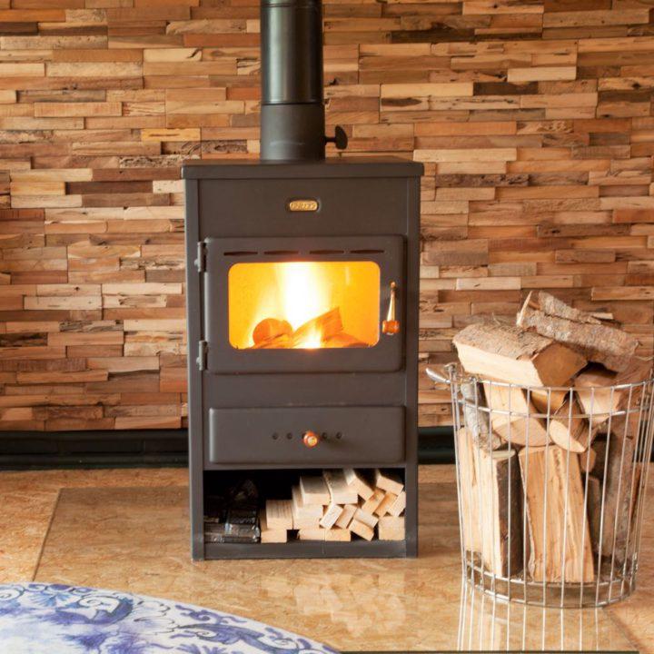 Brandende houtkachel met mand met hout