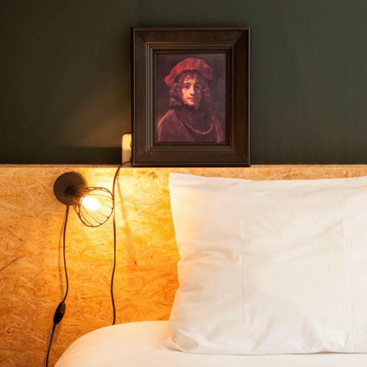 Bedhoofd met groene wand en schilderij erboven