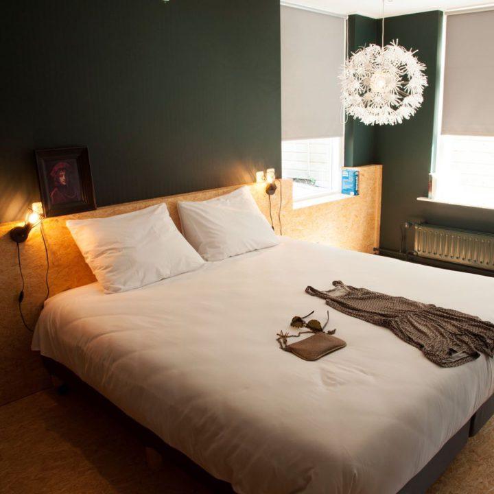 Tweepersoons slaapkamer met houten wand en donkergroene wanden