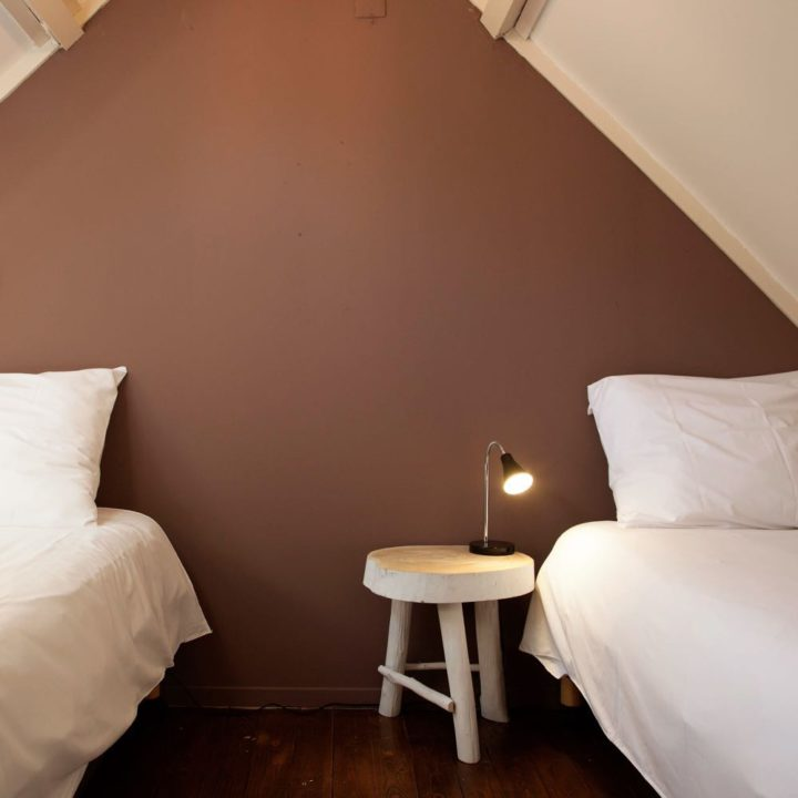 Onder een schuin dak staan twee bedden met witte dekbedden