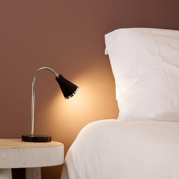 Close up van bedhoofd met wit kussen en zwart bedlampje