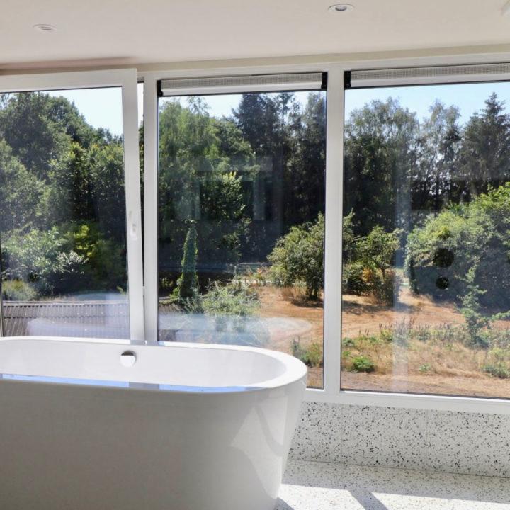 Vrijstaand bad voor grote ramen met uitzicht op natuur