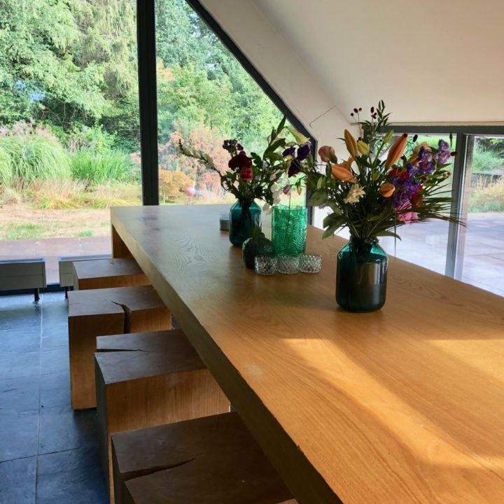 Lange houten eettafel met bos bloemen erop en houten krukken/blokken er om heen