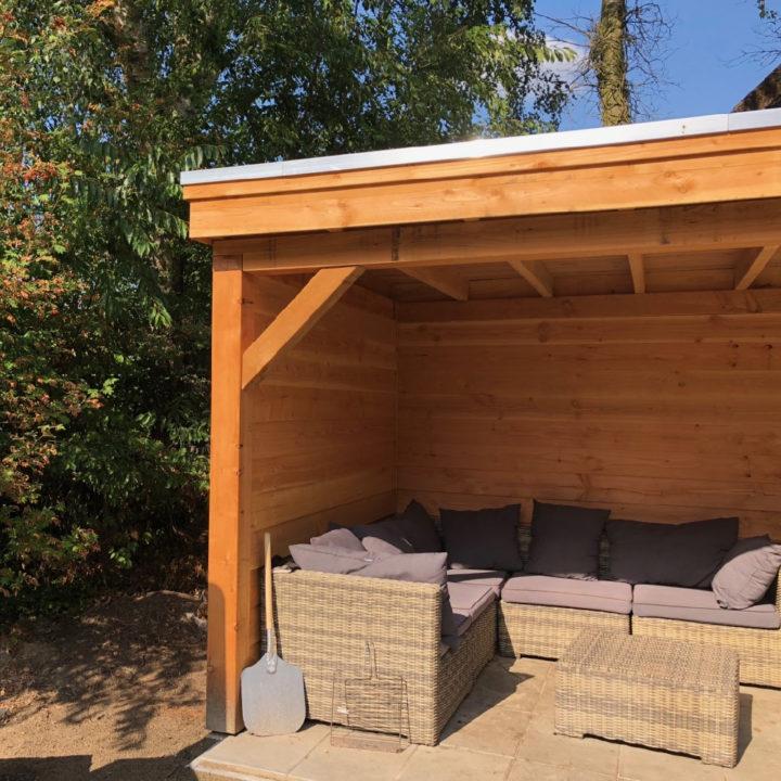 Een overkapping met loungebanken in de tuin van Huize Hulshorst