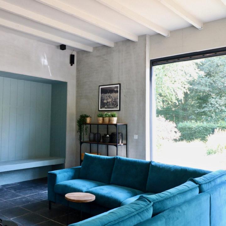 Blauwe hoekbank in de woonkamer van Huize Hulshorst