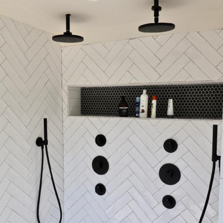 Dubbele douchekoppen naast elkaar in wit betegelde badkamer
