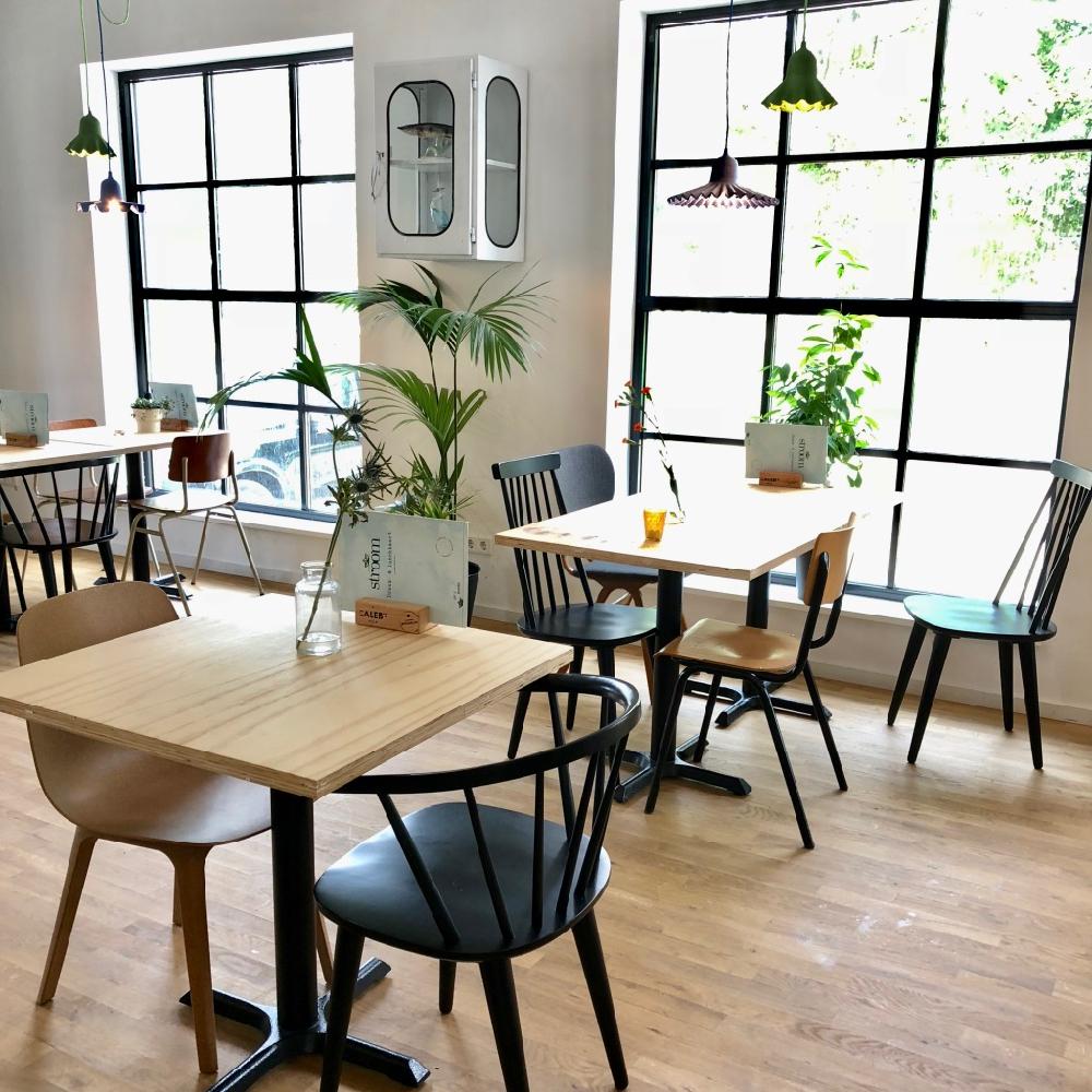 De hoge zaal met naturel kleurige tafels, verschillende stoelen en grote stalen ramen.