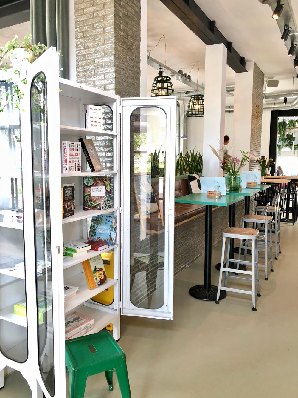 Een witte metalen boekenkast met bestsellers, prentenboeken en kookboeken bij Stroom Lent.