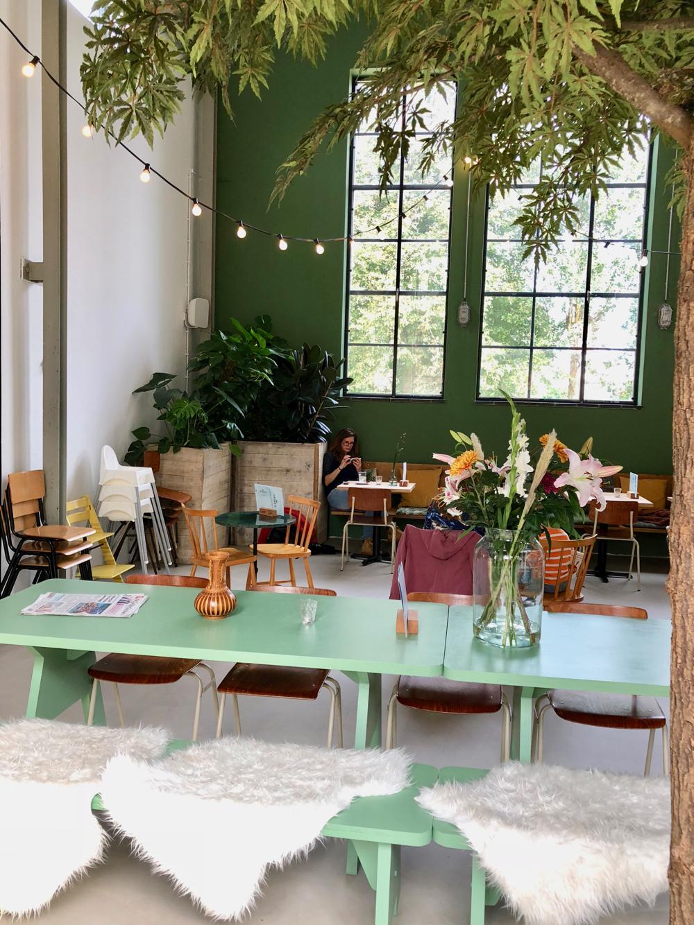 Groene tafel met bloemen tegen een groene achterwand met hoge stalen ramen.