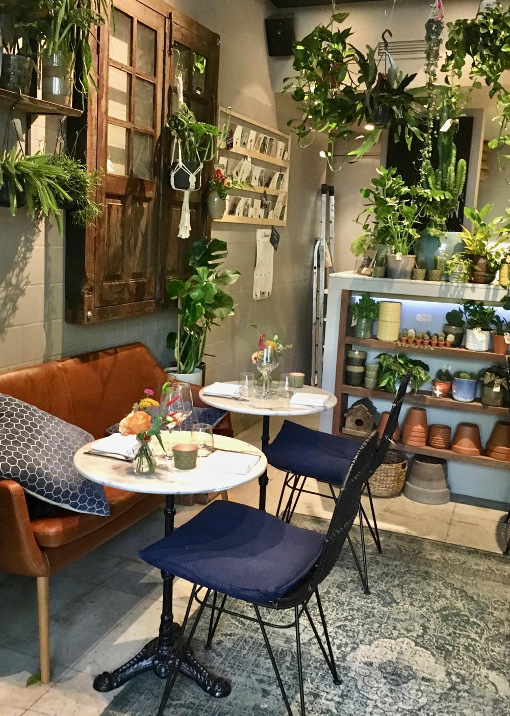 Ronde witte tafeltjes met blauwe stoelen tegen een wand vol groen
