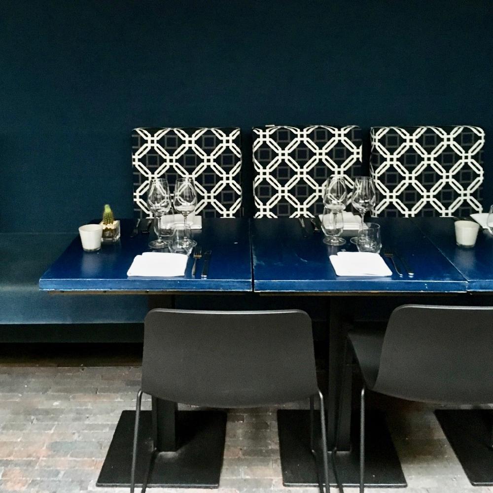 Een donkerblauwe wand met tafels en stoelen er voor in het restaurant gedeelte van Le jardin Utrecht