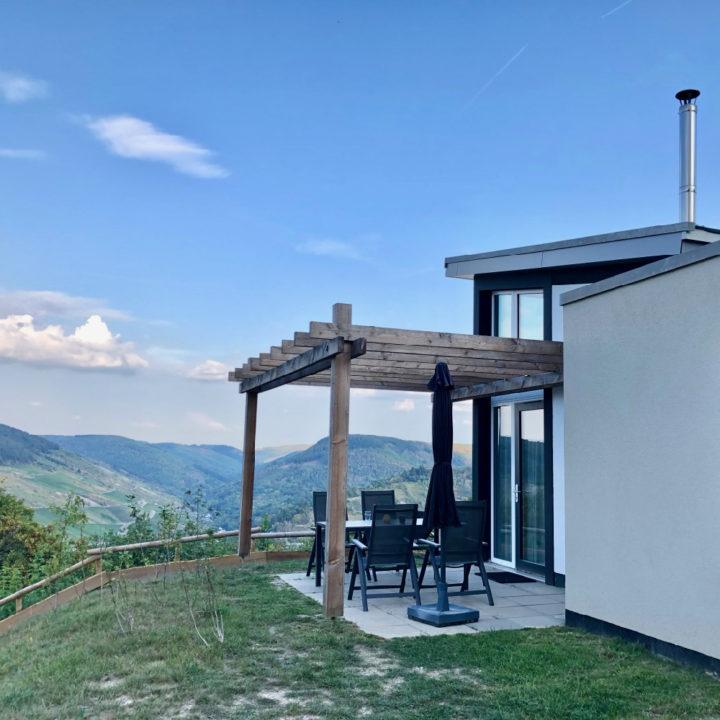 Zijkant van vakantiehuis, met terras en uitzicht over heuvels