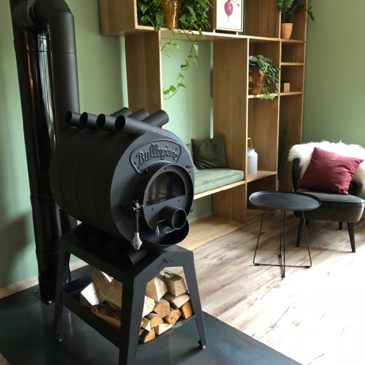 Zwarte houten kachel met houtblokken en fauteuil