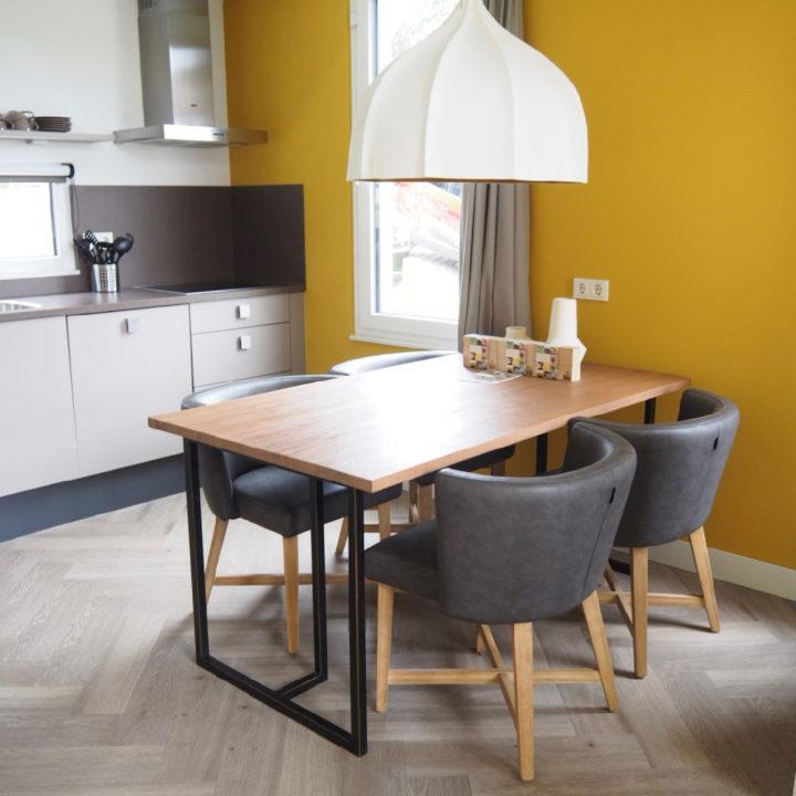 Gele muur, keukenblok en eettafel met vier stoelen