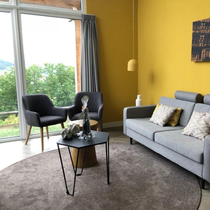 Grijs kleed, grijze bank, twee fauteuils en gele wand