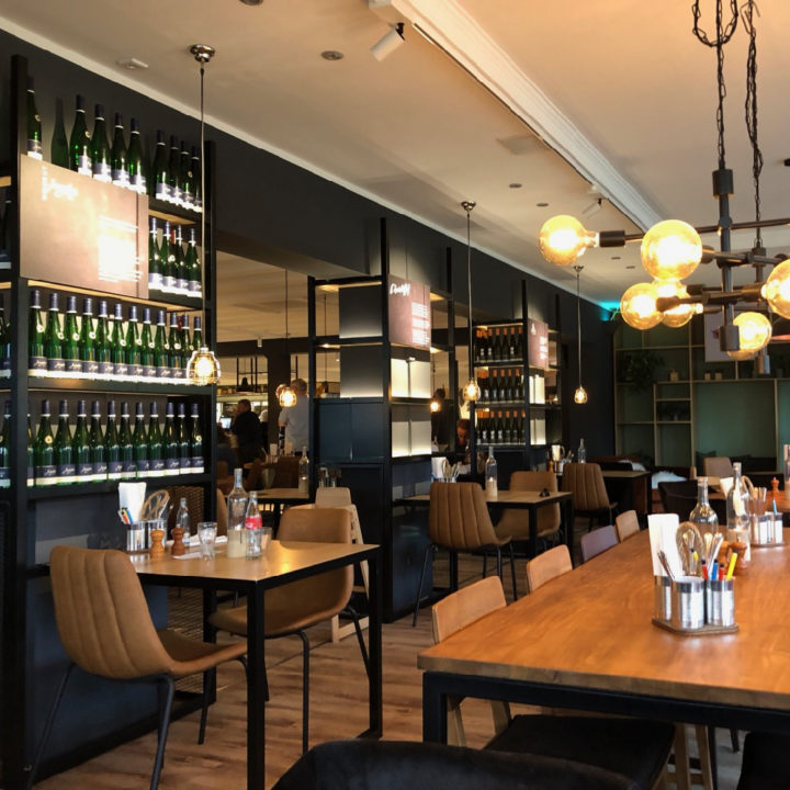 Sfeervolle ruimte met tafels en stoelen, een wand vol wijnflessen