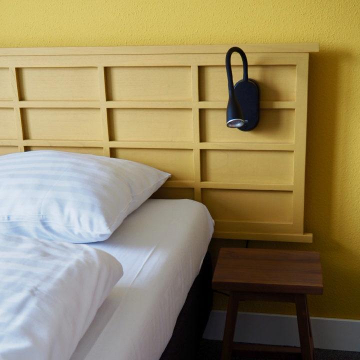 Wit opgemaakt bed, gele achterwand, zwart bedlampje