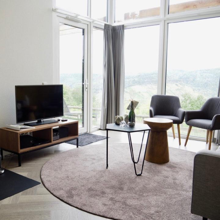 Woonkamer met grote ramen, een tv, salontafels en grijze stoeltjes