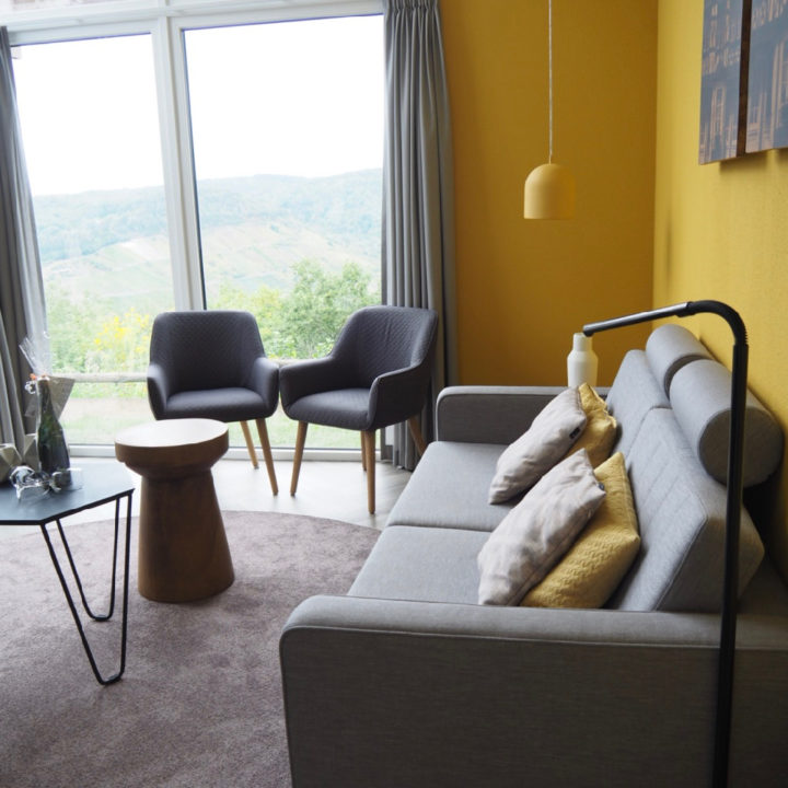 Woonkamer met grijze bank, 2 grijze fauteuils en een gele wand. Grote ramen met uitzicht op de Moezelvallei.
