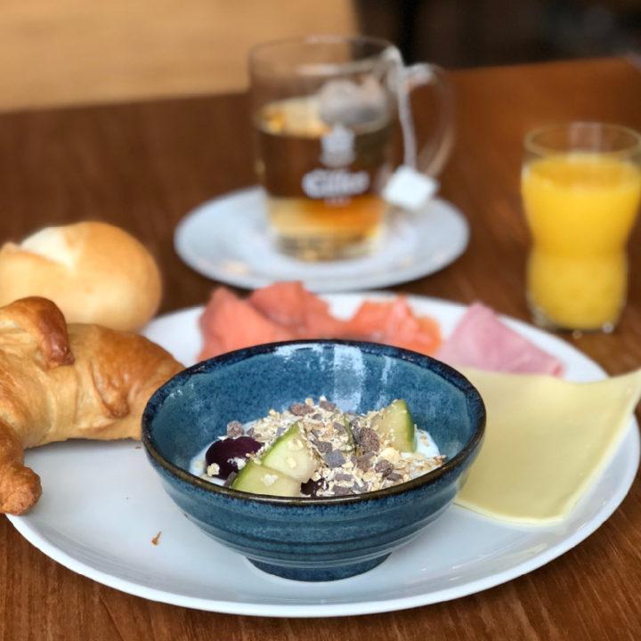 Wit bord, blauw schaaltje met yoghurt, jus d'orange, croissant