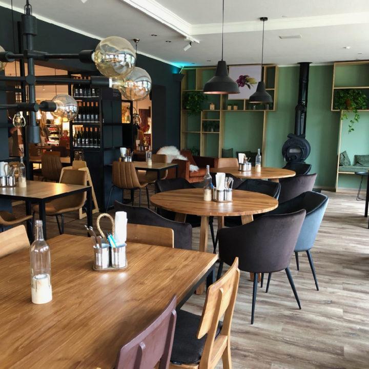 Tafels met stoelen, groene wand, wijnrekken